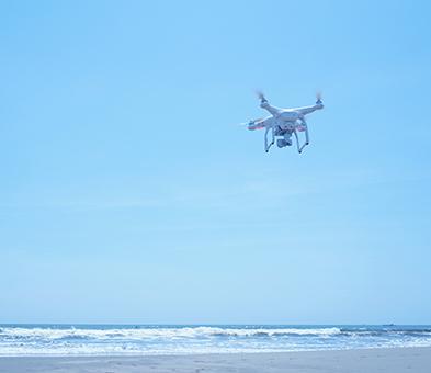 海辺を飛んでるドローンの画像